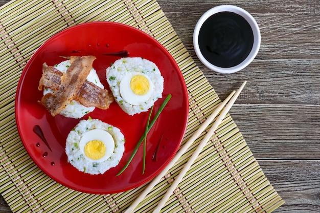 Gekochte eier eingewickelt in reis mit frühlingszwiebeln mit speckscheiben auf einem roten teller. frühstück im asiatischen stil. die draufsicht