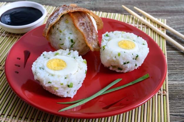 Gekochte eier eingewickelt in reis mit frühlingszwiebeln mit speckscheiben auf einem roten teller. frühstück im asiatischen stil.