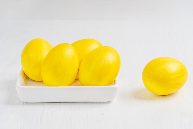 Gekochte eier gemalt in der leuchtend gelben farbe, die in der rechteckigen platte des porzellans an der osterparty liegt