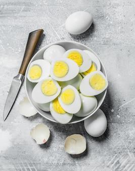 Gekochte eier in einer schüssel. auf einem rustikalen hintergrund.