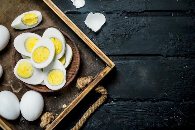 Gekochte eier in einer schüssel. auf einem schwarzen rustikalen hintergrund.