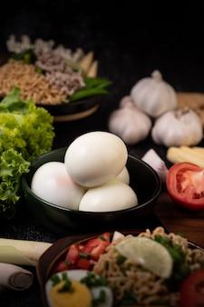 Gekochte eier in einer schwarzen schüssel, knoblauch, wurst, tomaten auf einem hölzernen schneidebrett