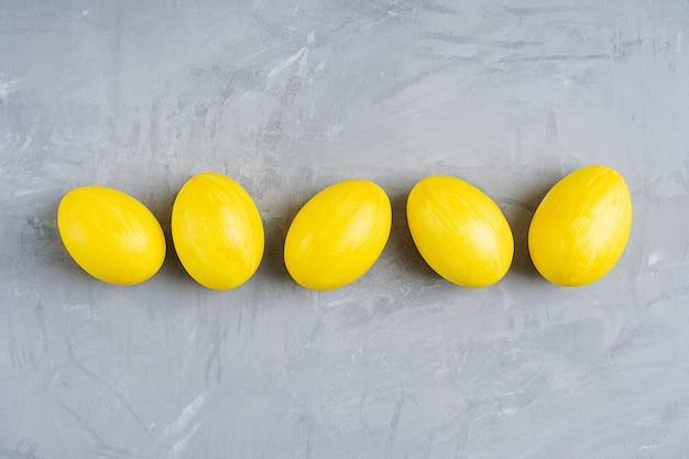 Gekochte eier in gelber farbe für ostern auf grauem betontisch in einer linie vorbereitet