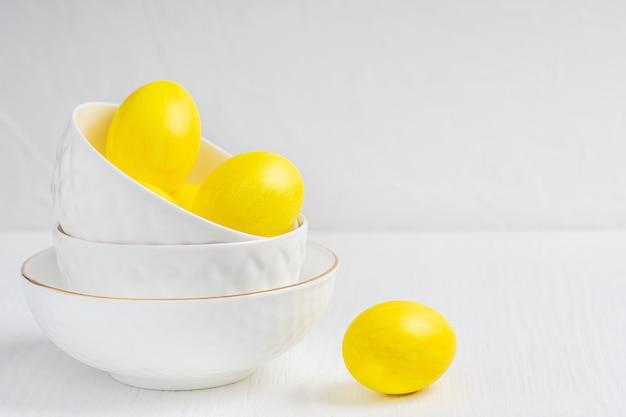 Gekochte eier in leuchtend gelber farbe in porzellanschalen, die zu ostern übereinander stehen
