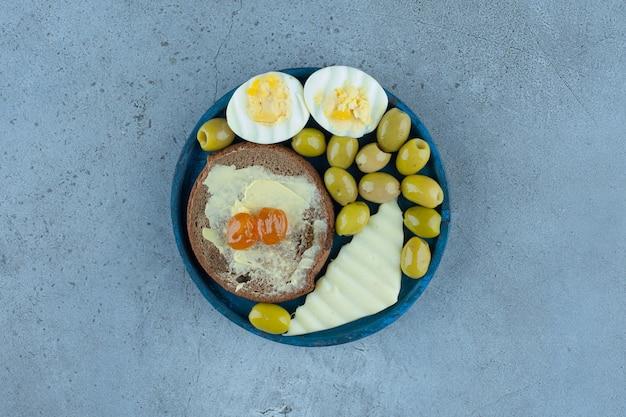 Gekochte eier, käsescheibe, butterbrot und grüne oliven auf einer blauen platte auf marmor.