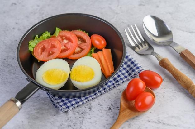 Gekochte eier, karotten und tomaten in einer pfanne mit tomaten auf einem holzlöffel.