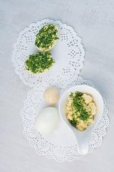 Gekochte eier mit grün auf weißem hintergrund.