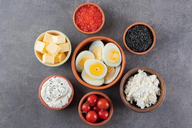 Gekochte eier mit rotem und schwarzem kaviar auf stein gelegt.