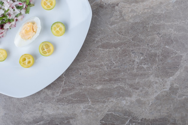 Gekochte eier mit salat als beilage auf weißem teller.