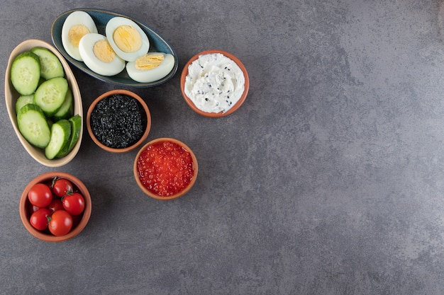 Gekochte eier mit würstchen und geschnittenen gurken auf steinhintergrund gelegt.