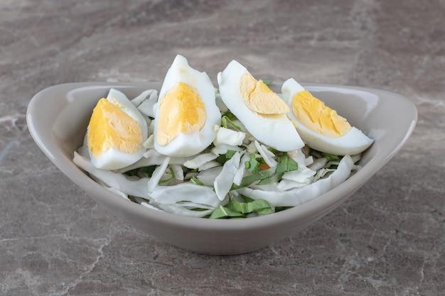 Gekochte eier und frischer salat in keramikschale.