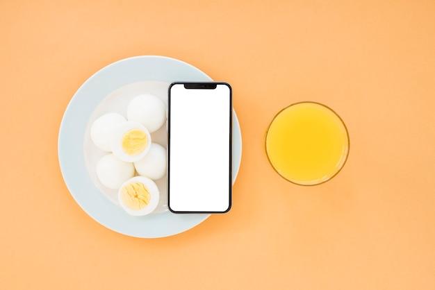 Gekochte eier und handy auf weißer platte mit orangensaftglas auf braunem hellem hintergrund