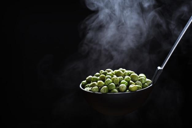 Gekochte erbsen in einer küchenkelle mit aufsteigendem dampf über einem dunklen hintergrund
