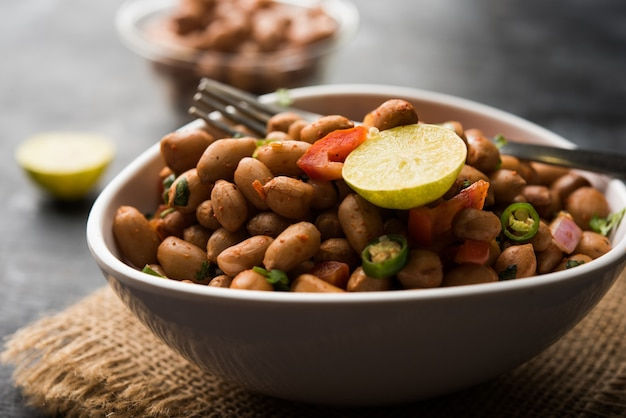 Gekochte erdnuss chaat oder chatpata singen dana oder shengdana oder mungfali. serviert in einer keramikschale über stimmungsvollem hintergrund