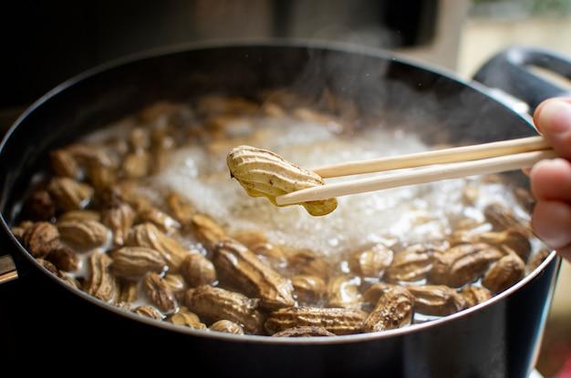 Gekochte erdnuss, erdnüsse gekocht in den essstäbchen mit kochenden erdnüssen