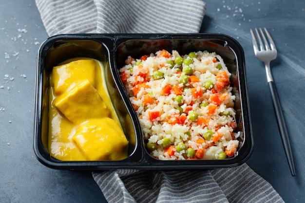 Gekochte fischstücke mit rohem gemüse und currysauce, serviert in einer lunchbox. nahaufnahme.