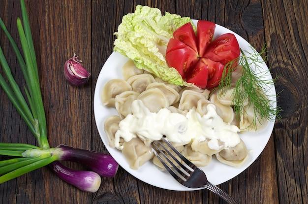 Gekochte fleischknödel, serviert mit sauerrahm-tomaten und frischen kräutern auf einem teller