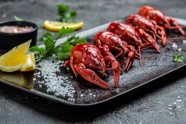 Gekochte flusskrebse oder langusten mit zitrone und salz essfertig auf schwarzem teller. restaurantmenü, diät, kochbuchrezept.