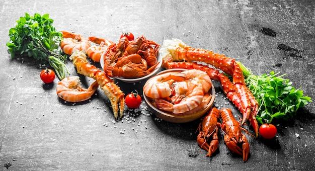 Gekochte garnelen, krabben und krebse mit kirschtomaten und kräutersträußen. auf dunklem rustikalem hintergrund