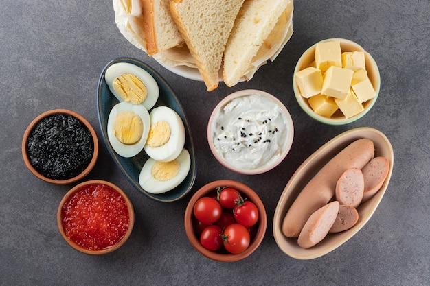 Gekochte geschnittene eier mit gewürzen auf steintisch gelegt.