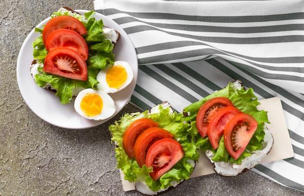Gekochte geschnittene eier und sandwiches mit frischkäse, tomaten und salat
