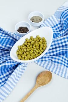 Gekochte grüne erbsen in einer weißen schüssel mit gewürzen, einem löffel und einer tischdecke.