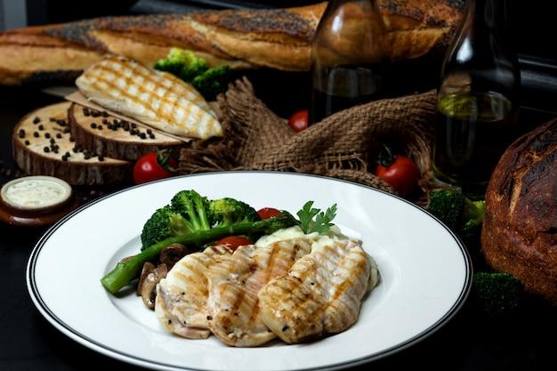 Gekochte hähnchenbrust mit brokkoli, champignons und tomaten