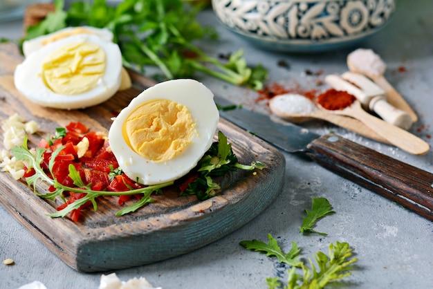 Gekochte hühnereier. der prozess des kochens gekochter marinierter hühnereier mit gemüse, kräutern, gewürzen und tomatensauce.