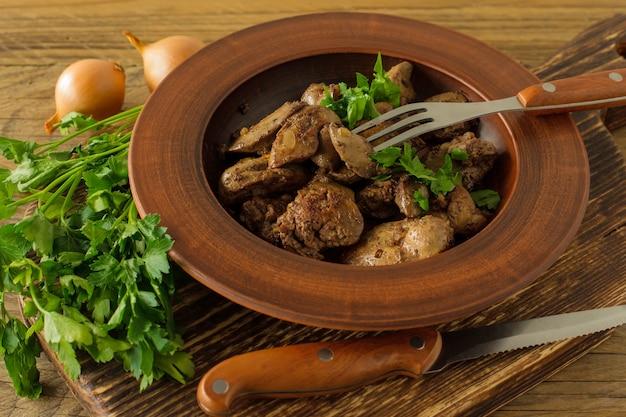 Gekochte hühnerleber mit zwiebeln auf einem teller serviert auf einem holzschreibtisch. rustikaler stil.