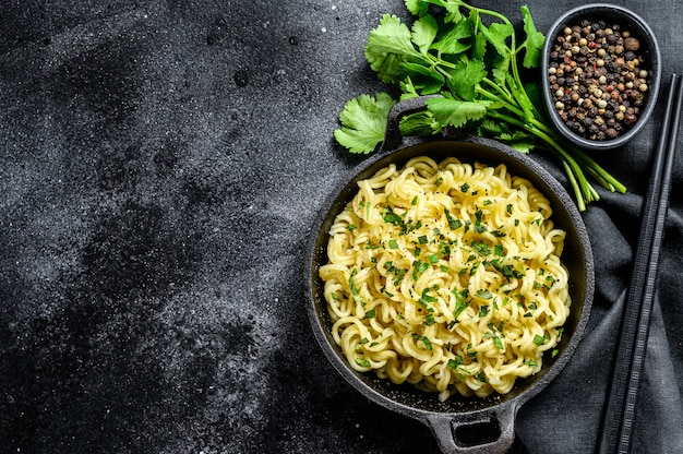 Gekochte instantnudeln mit sojafleisch in einem topf. vegetarisches gericht. schwarzer hintergrund. draufsicht. speicherplatz kopieren
