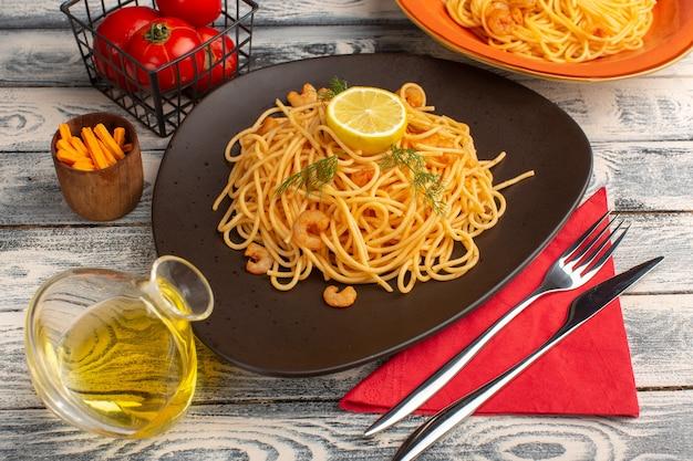 Gekochte italienische nudeln mit garnelengrün und zitrone in brauner platte auf grau