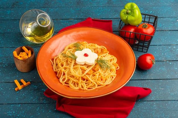 Gekochte italienische nudeln mit gemüse in orangefarbenem teller mit öl und gemüse auf blauem holz