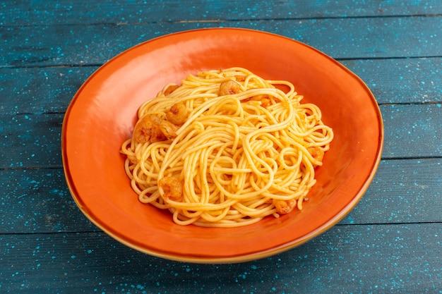 Gekochte italienische pasta lecker in orange platte auf blauem holz
