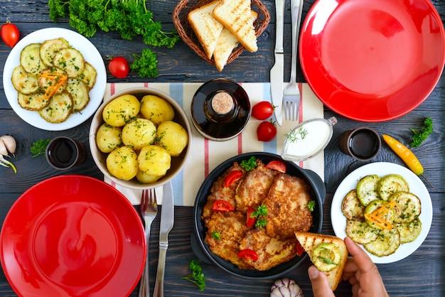 Gekochte junge kartoffeln, gebratene zucchinischeiben, schnitzel auf einem holztisch. draufsicht. serviert tisch für familienessen, mittagessen. rustikaler stil