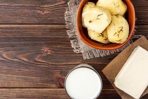 Gekochte kartoffel in brauner schüssel auf dunklem holz