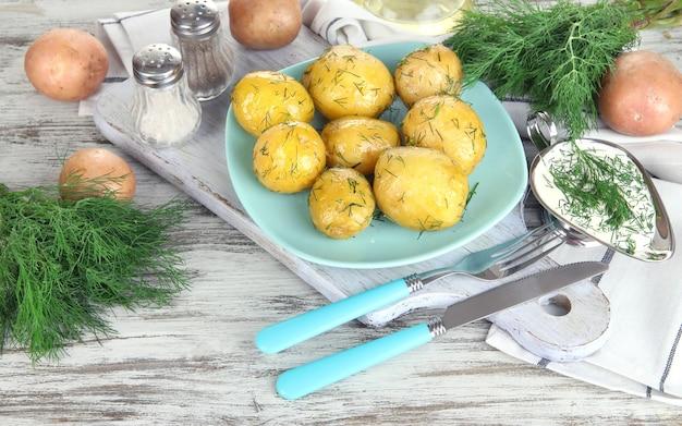 Gekochte kartoffeln auf platte auf holzbrett in der nähe von serviette auf holztisch