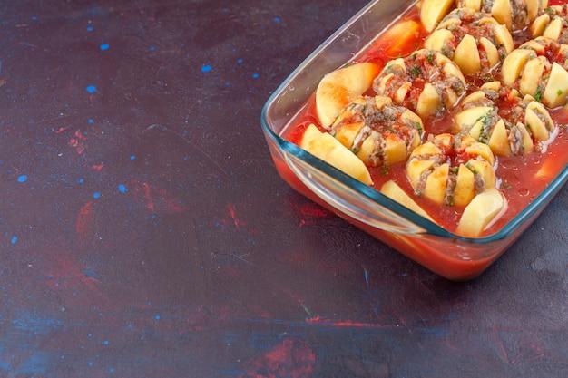 Gekochte kartoffeln der halben draufsicht mit soße und hackfleisch auf dunklem hintergrund.