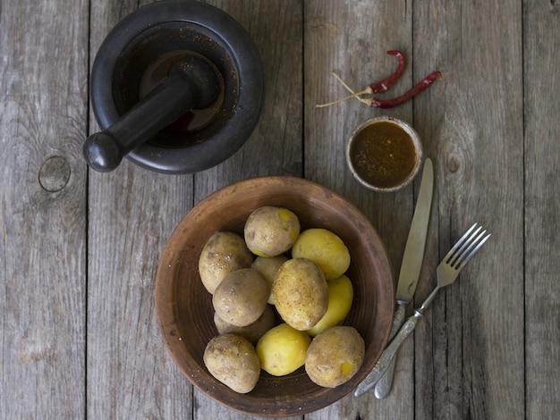Gekochte kartoffeln in ihren schalen. ganz mit rotem pfeffer, salz und würziger soße auf tonplatte, alter holztisch, rustikaler stil. nahaufnahme, platz kopieren. ansicht von oben.