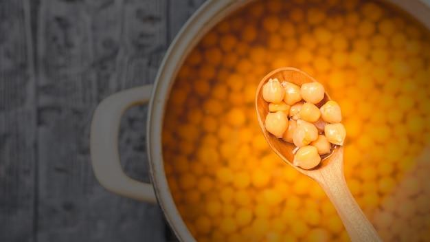Gekochte kichererbsen in einem holzlöffel. vegetarische küche aus hülsenfrüchten. der blick von oben. Premium Fotos