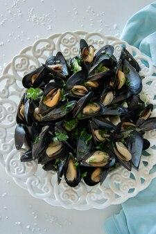 Gekochte köstliche schwarze muschel salziger weißer hintergrund gesundes ernährungskonzept reiches proteinlebensmittel