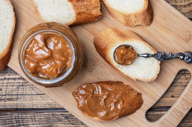 Gekochte kondensmilch mit einem glas auf einem holztisch. süße paste auf brotscheiben zum frühstück und dessert.