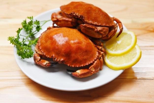 Gekochte krabbe auf platte mit zitronenkräutern und -gewürzen auf den hölzernen meeresfrüchten kochte roten steinkrabbensalat
