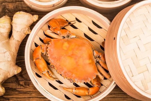 Gekochte krabben auf dampfgarer und holzbrettern