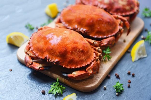 Gekochte krabben auf hölzernem brett mit zitrone auf platte dienten auf draufsicht der dunklen platte - gedämpfte meeresfrüchte der steinkrabbe