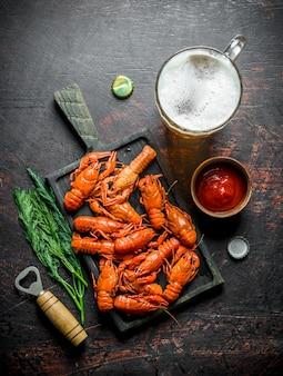 Gekochte krebse auf einem schneidebrett mit bier und tomatensauce auf rustikalem tisch