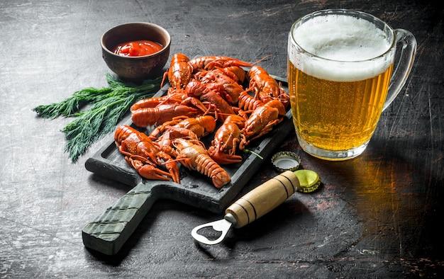 Gekochte krebse mit bier, dill und sauce auf dunklem rustikalem tisch
