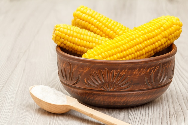 Gekochte maiskolben in tonschüssel und holzlöffel mit salz auf grauen brettern.