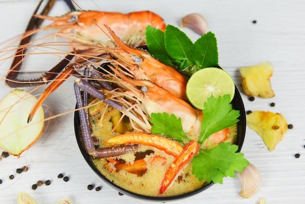 Gekochte meeresfrüchte des thailändischen lebensmittels tom yum kungs asiatische traditionelle würzige suppenschüssel der garnele mit garnelensuppen-abendtisch und gewürzbestandteilen