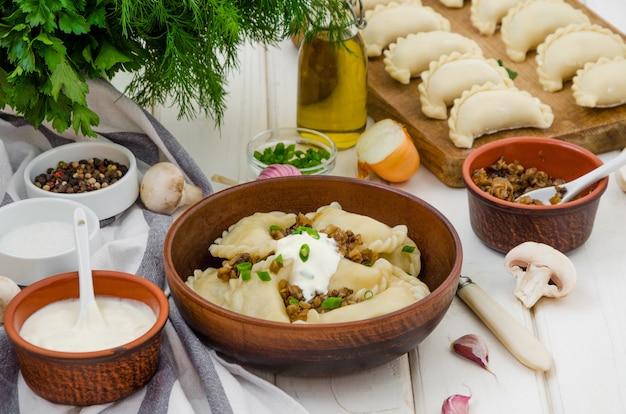 Gekochte mehlklöße (vareniki) mit kartoffeln und gebratenen pilzen mit zwiebeln in einer schüssel mit sauerrahm und frühlingszwiebeln auf einem weißen hölzernen hintergrund.