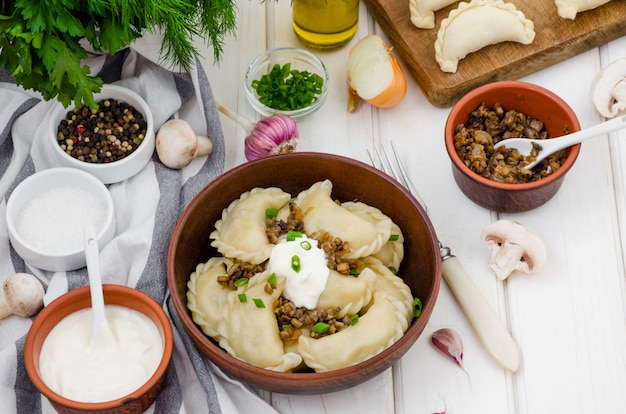 Gekochte mehlklöße (vareniki) mit kartoffeln und gebratenen pilzen mit zwiebeln in einer schüssel mit sauerrahm und frühlingszwiebeln auf einer weißen holzoberfläche